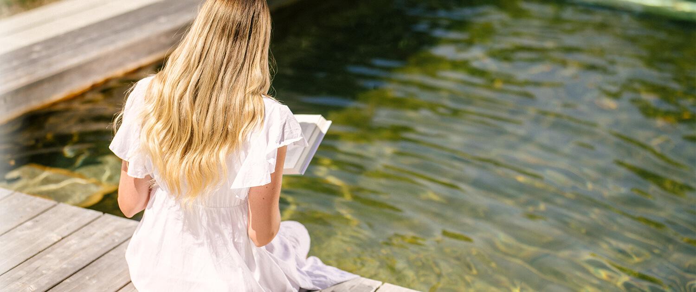 Dame liest ein Buch am Holc Naturpool und hält die Beine ins Wasser.