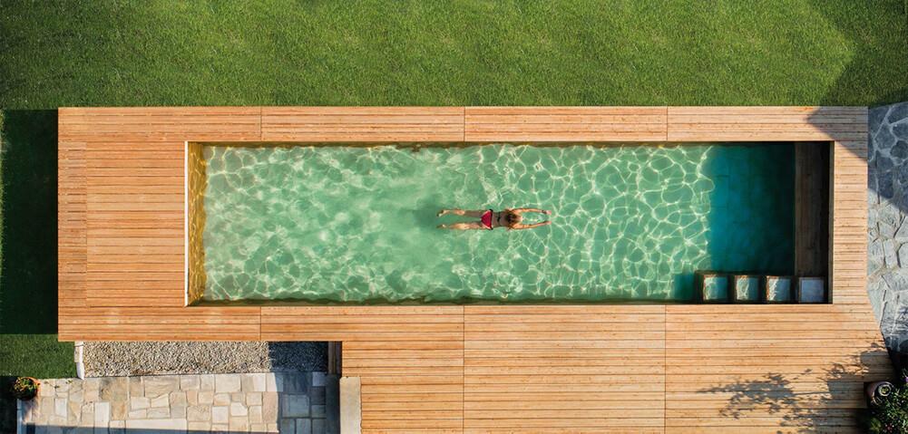Dame schwimmt im Holc Naturpool. Gesundes Wasser, keine Chemie, einfach nur pures Schwimmvergüngen.