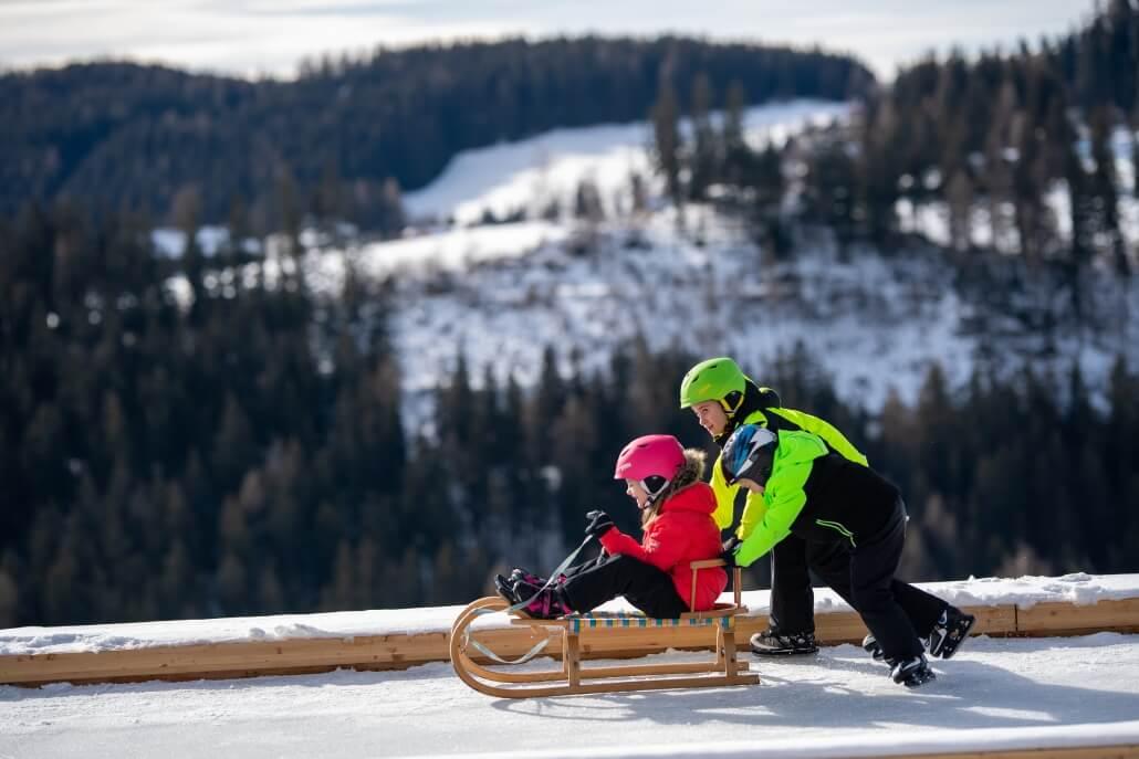 Kinder spielen am Holc Naturpool im Winter, mit Eis