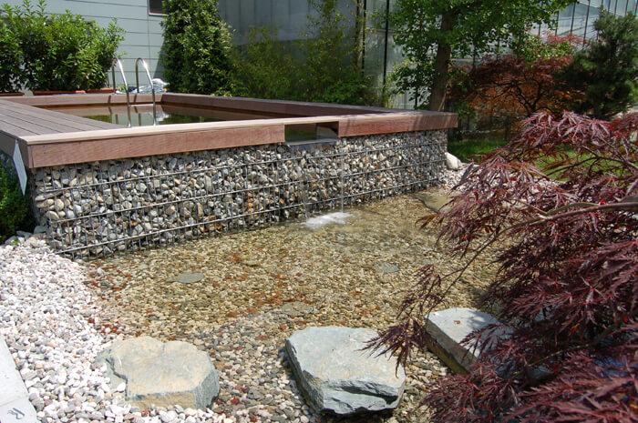 Garten mit Holc Naturpool und Steinmauer